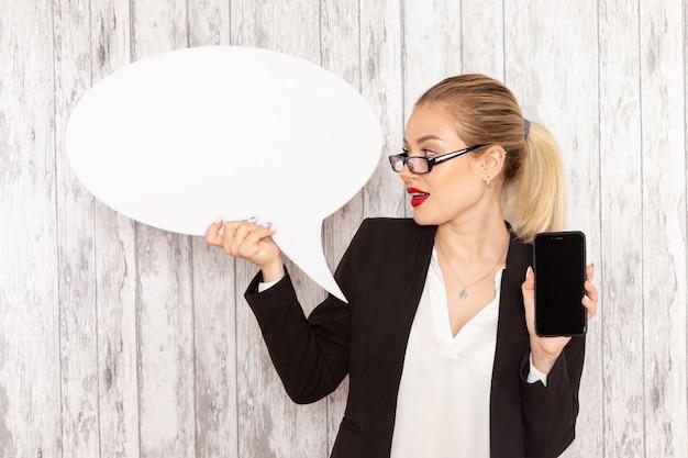 Vista frontal jovem empresária em roupas restritas, jaqueta preta segurando seu telefone e uma placa branca na superfície branca
