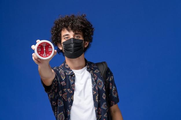 Vista frontal jovem estudante do sexo masculino usando máscara preta com mochila segurando relógios sobre o fundo azul.