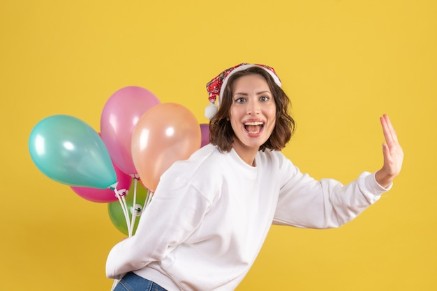 Vista frontal jovem feliz escondendo balões coloridos ano novo natal cor férias mulher emoção