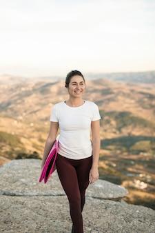 Vista frontal jovem fêmea com tapete de ioga