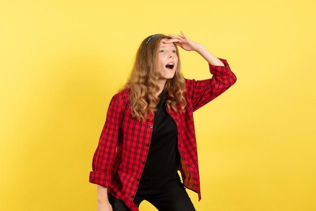 Vista frontal jovem fêmea em camisa quadriculada vermelha olhando para a distância em fundo amarelo mulher emoção humana modelo moda garota