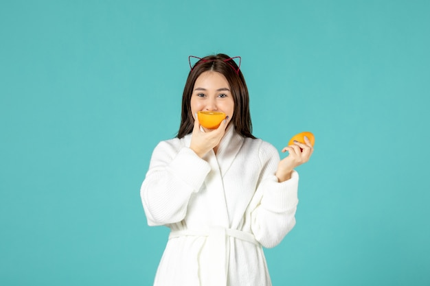 Vista frontal jovem fêmea em roupão segurando uma fatia de laranja sobre fundo azul
