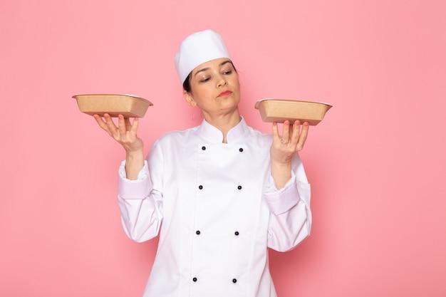 Vista frontal, jovem, femininas, cozinheiro, em, cozinheiro branco, paleto, branca, boné, posar, segurando, leite, marrom, tigelas