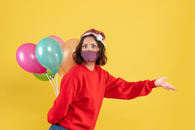 Vista frontal jovem feminino escondendo balões em máscara estéril natal férias cor emoção mulher ano novo