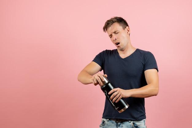 Vista frontal jovem homem com camisa azul escura segurando uma garrafa térmica na cor do modelo de emoção homem masculino humano de fundo rosa