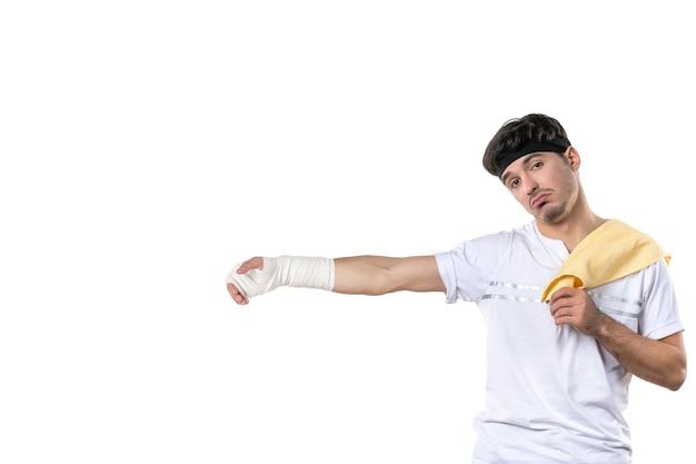 Vista frontal jovem homem com curativo na mão machucada no fundo branco dieta esporte dor estilo de vida lesão corporal ajuste atleta ginásio hospital