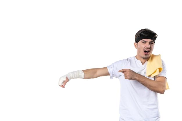 Vista frontal jovem homem com curativo na mão machucada no fundo branco dieta esporte dor estilo de vida lesão corporal ajuste ginásio hospital