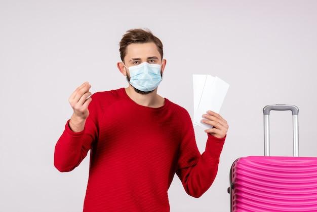 Vista frontal, jovem homem com máscara estéril segurando bilhetes na parede branca viagem covid- viagem férias cor emoções vírus voo