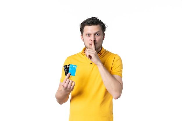 Vista frontal jovem homem de camisa amarela segurando um par de cartão do banco pedindo para ficar em silêncio sobre fundo branco uniforme trabalho gastando dinheiro cor trabalhador humano