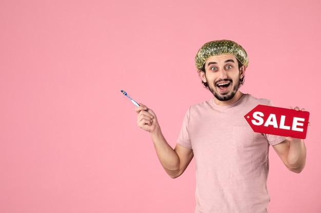 Vista frontal jovem homem limpando os dentes e segurando a placa de identificação de venda no fundo rosa