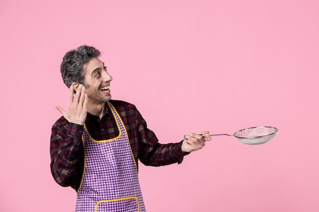 Vista frontal jovem homem na capa segurando a peneira no fundo rosa trabalhador cozinheiro trabalho profissão marido horizontal cor cozinha