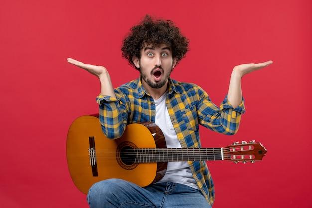 Vista frontal jovem homem sentado e tocando guitarra na parede vermelha concerto ao vivo músico aplausos banda tocar música cor