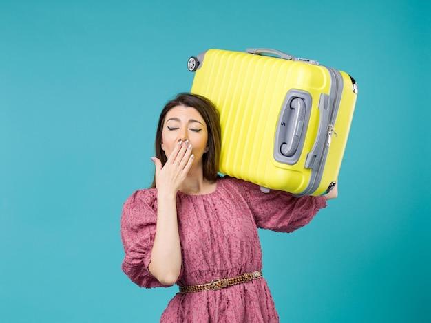 Vista frontal jovem indo de férias com seu grande saco no fundo azul viagem de verão mulher mar viagem de férias
