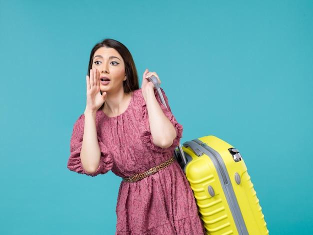 Vista frontal jovem indo de férias com sua bolsa amarela na viagem de fundo azul viagem de verão mulher mar humano