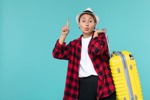 Vista frontal jovem indo de férias com sua bolsa amarela no piso azul viagem viagem menina viagem mar