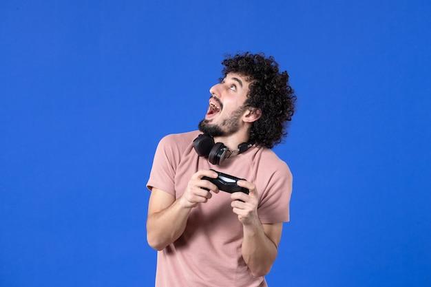 Vista frontal jovem jogando videogame com gamepad preto sobre fundo azul adolescente jovem ganhando sofá adulto alegria virtual jogador de futebol