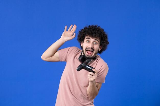 Vista frontal jovem jogando videogame com gamepad preto sobre fundo azul jovem adolescente ganhando jogador de futebol adulto virtual alegria