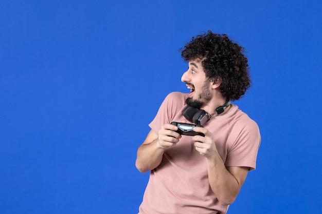 Vista frontal jovem jogando videogame com gamepad preto sobre fundo azul virtual adolescente jovem jogador de futebol adulto ganhando alegria