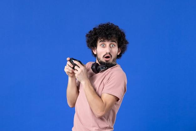 Vista frontal jovem jogando videogame com gamepad preto sobre fundo azul virtual adolescente jovem sofá adulto alegria jogador vencendo