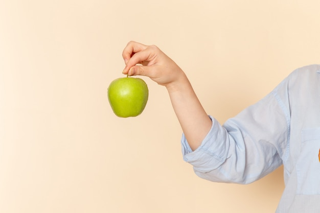 Vista frontal jovem linda mulher com camisa segurando maçã verde fresca na parede creme fruta modelo mulher pose
