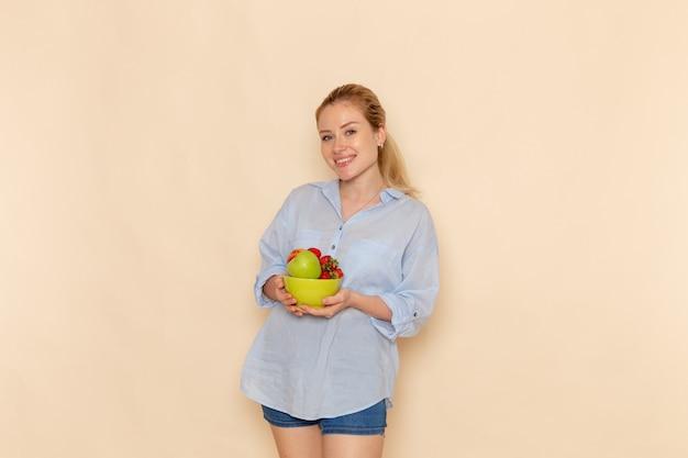 Vista frontal jovem linda mulher com camisa segurando o prato com frutas na parede creme fruta modelo maduro mulher pose