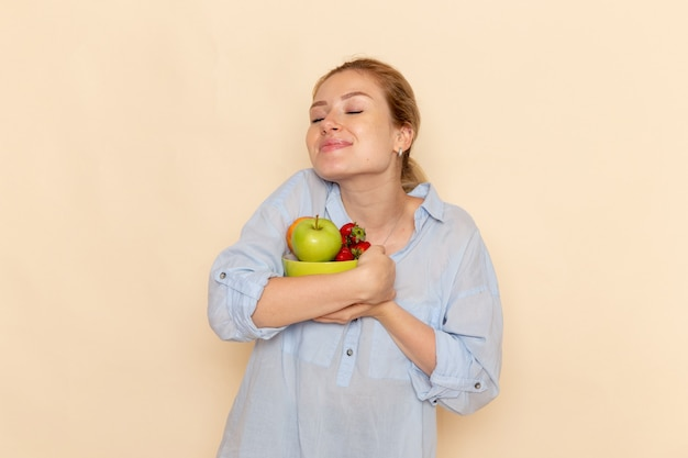 Vista frontal jovem linda mulher com camisa segurando o prato com frutas na pose de mulher modelo de frutas de parede creme claro
