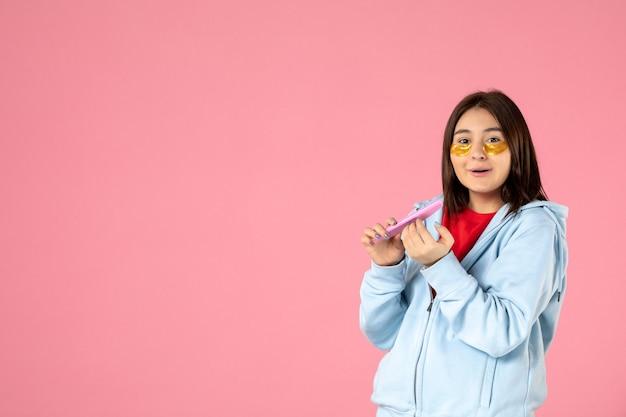 Vista frontal jovem, linda mulher, com tapa-olho fazendo as unhas em fundo rosa