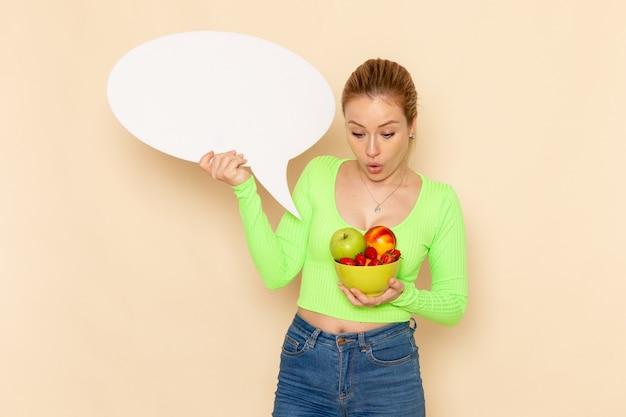 Vista frontal jovem linda mulher de camisa verde segurando o prato cheio de frutas e placa branca na parede creme modelo de frutas mulher vitamina alimentar