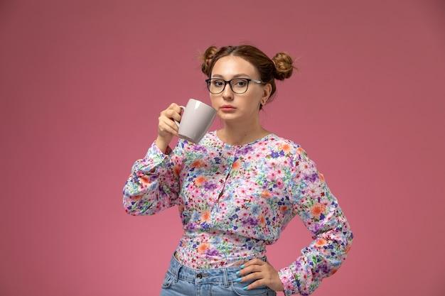 Vista frontal jovem linda mulher em camisa com design de flor e jeans azul, bebendo chá, posando no fundo rosa