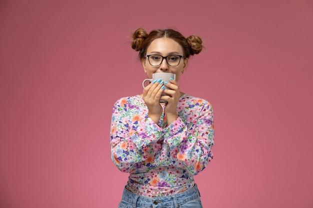 Vista frontal jovem linda mulher em camisa com design flor e calça jeans, bebendo um chá, sorrindo no fundo rosa