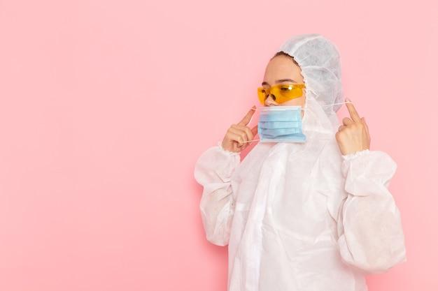 Vista frontal jovem linda mulher em um terno branco especial usando máscara estéril no espaço rosa especial.