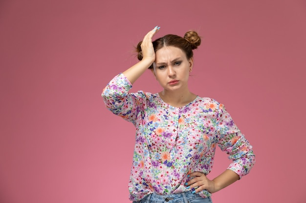 Vista frontal jovem linda mulher em uma camisa com design flor e calça jeans, tendo dor de cabeça no fundo rosa