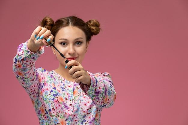Vista frontal jovem linda mulher em uma camisa com design flor e jeans azul segurando rímel no fundo rosa