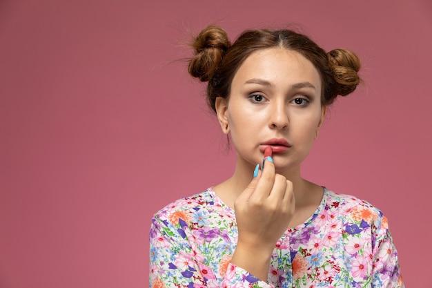 Vista frontal jovem linda mulher em uma camisa com design floral e jeans azul fazendo maquiagem na mesa rosa