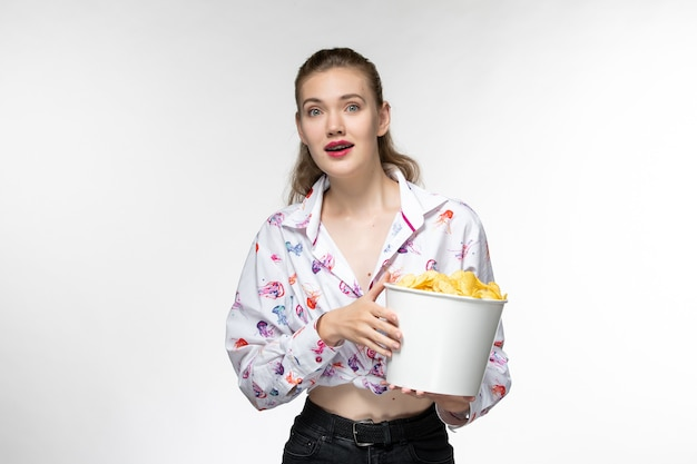 Vista frontal jovem linda mulher segurando batatas cips assistindo filme na superfície branca