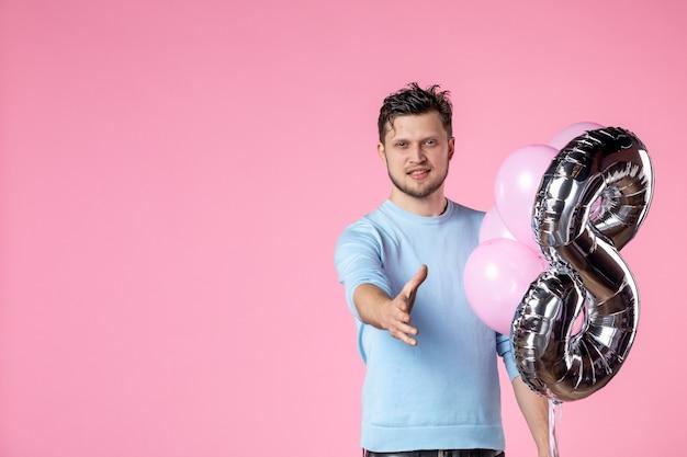 Vista frontal jovem macho com balões fofos como presente de marcha tentando apertar as mãos no fundo rosa feminino feminino dia sensual data amor casamento igualdade
