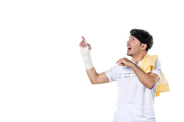 Vista frontal jovem macho com bandagem na mão machucada no fundo branco dieta esporte dor estilo de vida lesão corporal ajuste atleta ginásio