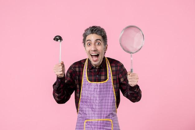 Vista frontal jovem macho na capa com peneira e colher no fundo rosa cozinheiro trabalhador profissão uniforme marido cozinha horizontal