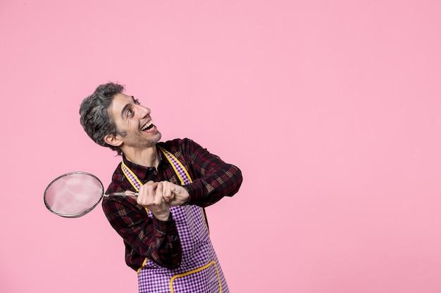 Vista frontal jovem macho na capa segurando peneira na cor de fundo rosa cozinheiro uniforme marido trabalhador trabalho profissão comida cozinha