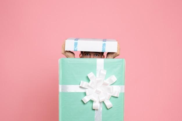 Vista frontal jovem macho tentando se esconder dentro da caixa de presente no natal rosa emoção dormir pijama jogo de festa