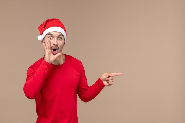 Vista frontal jovem masculino chamando no fundo marrom emoção feriado de natal