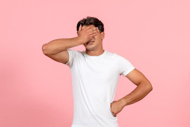 Vista frontal jovem masculino cobrindo o rosto em uma camiseta branca em fundo rosa cor masculina modelo emoção