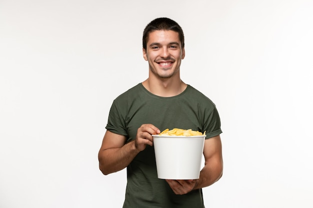 Vista frontal jovem masculino com camiseta verde com batata cips assistindo filme e sorrindo na parede branca filme pessoa masculino filme solitário cinema