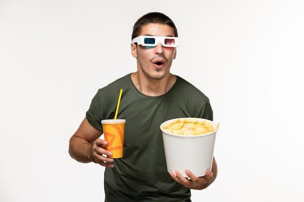 Vista frontal jovem masculino com camiseta verde segurando batata cips e refrigerante em óculos de sol d em filme de parede branca filme de solitário masculino