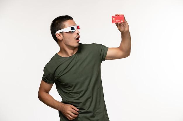 Vista frontal jovem masculino com camiseta verde segurando o cartão do banco em óculos de sol d em filme de cinema solitário de parede branca clara