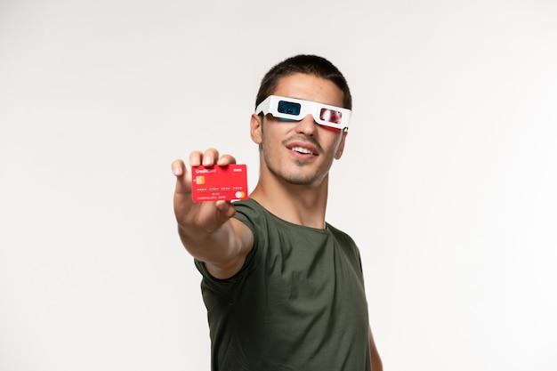 Vista frontal jovem masculino com camiseta verde segurando o cartão do banco em óculos de sol d em filme de parede branco claro filmes de cinema solitário