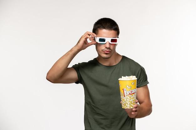 Vista frontal jovem masculino com camiseta verde segurando pipoca e óculos de sol assistindo filme na mesa branca filme solitário cinema masculino filmes