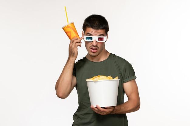 Vista frontal jovem masculino com camiseta verde segurando refrigerante de batata cips em óculos de sol d na parede branca filme filme cinema solitário masculino