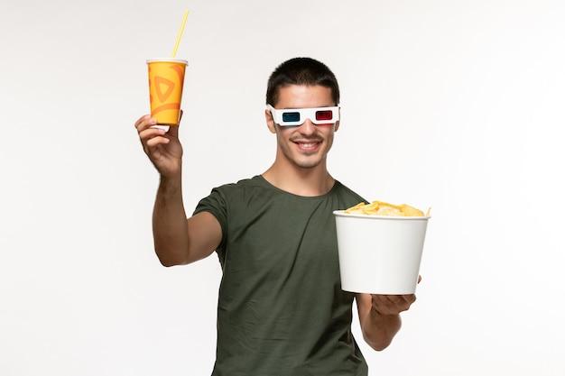 Vista frontal jovem masculino com camiseta verde segurando refrigerante de batata cips em óculos de sol na parede branca filme masculino solitário cinema