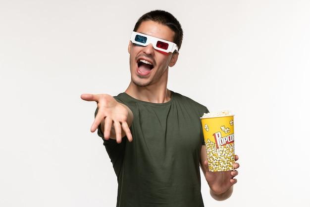 Vista frontal jovem masculino com camiseta verde segurando um pacote de pipoca em óculos de sol d na parede branca filme cinema solitário masculino